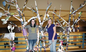 Photos by Jenny Neyman, Redoubt Reporter. Sadie Averill, left, and Heidi Kaser, seniors at Nikiski Middle-High School, assembled trees from the political flyers that stuffed mailboxes this election season. Art teacher Anna Widman had each of her classes construct branches for the trees.