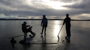 Matt Neisinger, left, Tom Seggerman and Tony Eskelin are silhouetted in the sun on Bottenintnin Lake on Saturday, swapping ice reports before heading out for some hockey.