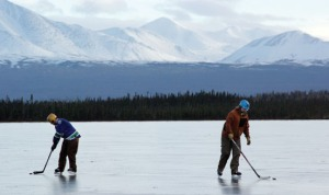 Photos by Jenny Neyman, Redoubt Reporter. Dan Balmer, left, and Matt Neisinger, both of Sterling, practice their hockey skills on Bottenintnin Lake on Saturday. Freezing temperatures with no snow creates conditions ripe for ice skating.