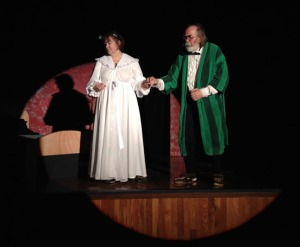 "Photos courtesy of Triumvirate Theatre. Ebenezer Scrooge (Allen Auxier) is led to some self-realization by the Ghost of Christmas Past (Terri Burdick) in Triumvirate Theatre's production of ""A Christmas Carol."""