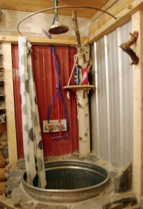 Johnson's approach to home improvements involves improving on found objects, like this shower stall made out of a feed tub with the shower head suspended by an old ice axe.