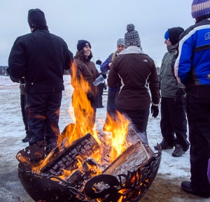 Photos courtesy of Joe Kashi. Attendees of Frozen River Festival on Saturday at Soldotna Creek Park warm themselves by a fire while sampling the many cold beverages on tap from 12 brewers and wineries in the state.
