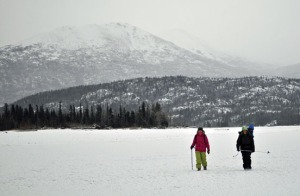 Photos by Joseph Robertia, Redoubt Reporter. Aagje Buzink, visiting from the United Kingdom, and Colleen and Lynx (in backpack) Robertia walk across frozen Skilak Lake recently, enjoying a winter day in a portion of the Kenai National Wildlife Refuge.