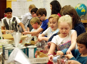 Photo by Jenny Neyman, Redoubt Reporter. Students at Soldotna Montessori School package bags of bean soup mix to be donated to the Kenai Peninsula Food Bank on Feb. 27.