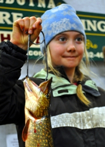 Photos by Joseph Robertia, Redoubt Reporter. Kylie Copenhaver, of Soldotna, holds up a pike she caught for the Trustworthy Hardware and Fishing 18th annual Ice Fishing Derby. Despite being a minor, she competed in the open division with adults and won the pike category with her 4.23-pound fish. The derby concluded over the weekend at the end of February.