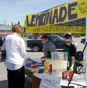 Photo by Jenny Neyman, Redoubt Reporter. Spencer Kapp, left, and Quinn Lucas operate their Lemonade to your Aid stand on the Kenai Spur Highway in front of Jo-Ann Fabric in Soldotna on the Kenai Spur Highway. More than a dozen stands popped up in the Kenai-Soldotna area on Lemonade Day in Alaska, a program that teaches kids about business.