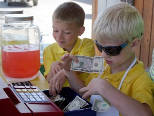 Parker and Eli Richards practice their accounting skills in making change for a customer at their stand in front of Wilderness Way in Soldotna.