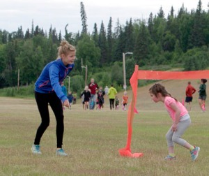 Salmon Run Series organizer Allie Ostrander directs Raylie Allemann to the finish line in a kids' race preceding the first community Salmon Run Series race of the summer July 8 at Tsalteshi Trails.