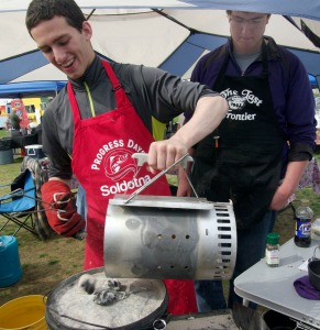 Brenner Musgrave shakes some hot coals onto a Dutch oven to cook his entree course.