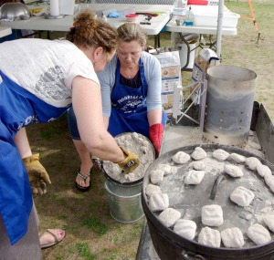 Molly Noyes, left, and Stephanie Ferguson rake coals off a lid of one of their pots so they can use it to serve their rolls to the judges. Their team, Buns in the Oven, won the adult division.