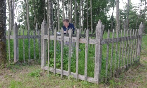 Photos by Jenny Neyman, Redoubt Reporter. Tracy Miller, president of the Totem Tracers genealogical society, examines the remains of the Kasilof Boat Harbor Cemetery. The group is trying to preserve the site and expound on its history.