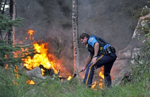 Photos by Joseph Robertia, Redoubt Reporter. Above, an Alaska State Trooper, the first responder on the scene, looks for survivors in the wreckage of a Cessna 180 that crashed in Kasilof on Saturday. Two people were aboard. There were no survivors. Below, Central Emergency Services firefighters extinguish the fire sparked by the crash at about 8:11 p.m.