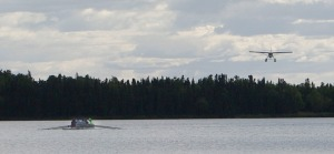 A floatplane glides in to land on Mackey Lake, with boat of rowers waiting for it to pass.