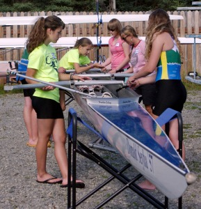 Team Chocolate Milk, with Alaska Midnight Sun Rowing Association's Laurie Winslow, right side, center, volunteering as coxswain, work on the rigging of their boat. Abby Moffett, in a pink shirt, a seventh-grader at Kenai Middle School, works next to Winslow.