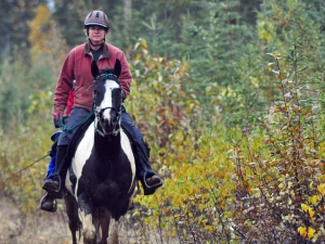 Jane Adkins rides along a trail of off the Escape Route in Nikiski on Saturday. Adkins came up with the idea of holding the inaugural Midnight Sun Challenge edurance ride, and organized the event.
