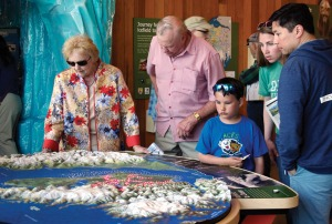 Redoubt Reporter file photo. Visitors check out a map at the grand opening of the Kenai National Wildlife Refuge Visitors Center earlier this year. Now that the busy summer season has passed, refuge staff are taking time to get new volunteers involved in various capacities.