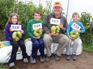 Photo courtesy of Patrick White. Patrick White, of Soldotna, and his grandkids, from left, Mackenzie, Ethan and Caleb, show off the biggest of the giant tomatoes they grew this summer. They set a new state record of 4.5 pounds with a tomato picked in early September for the Alaska State Fair, and entered these four in the world tomato competition.