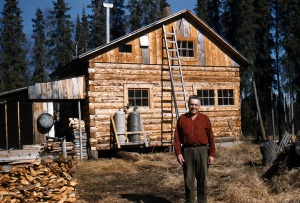 Photo by Ray Sandstrom, courtesy of the Kenai Peninsula Historical Photo Repository. Howard J. Binkley poses in 1952 in front of a log house on his homestead property in Soldotna. The two-story structure had a propane cookstove complemented by a good woodpile. Early in the 21st century, this structure was moved to a location off East Redoubt Avenue and was nicely restored. Binkley spent only a handful of years in this home before returning to his native Pennsylvania.