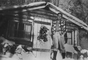 Photo courtesy of the Kenai Peninsula. Historical Photo Repository. Jack Farnsworth stands outside the family's cabin in the early days of Soldotna.