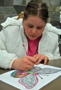 Photo by Joseph Robertia, Redoubt Reporter. Briley Morton of Soldotna completes her butterfly during an adult coloring program at the Soldotna Public Library last week. Adult coloring is becoming popular at libraries across the country.