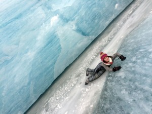 Sabina Morin slides off a chunk of crystal-clear ice near the edge of Grewingk Glacier.