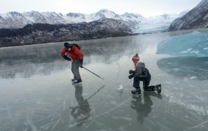 Photos by Cary Restino, Homer Tribune. Daniel Perry and Sabina Morin play with a chunk of ice while skating on the frozen lake at the toe of Grewingk Glacier across Kachemak Bay from Homer last week.