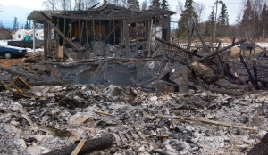 Photos by Jenny Neyman, Redoubt Reporter. The shell of a home at 1211 Lilac Lane stands beyond the complete wreckage of a home at 1213 Lilac that exploded from a natural gas leak caused by the magnitude 7.1 earthquake Sunday.