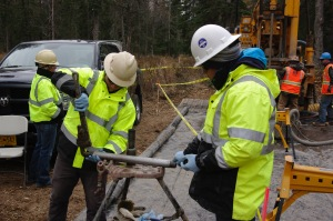 Redoubt Reporter file photo, Contractors for the AK LNG project conduct fieldwork taking ground samples in Nikiski in October 2014. The project hasn't yet started up its expected fieldwork this season.