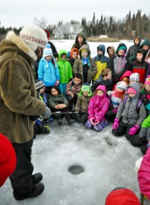 Photo by Joseph Robertia, Redoubt Reporter. Carmen Field, an aquatic educator with Fish and Game, explains to the kids how to use ice-fishing rods prior to turning them loose on Sport Lake.