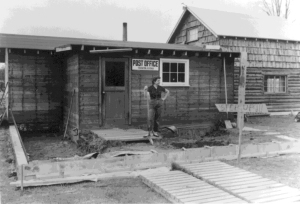 Photo courtesy of the KPC Historical Photo Archive. Mickey Faa, who succeeded Maxine Lee as the postmaster of Soldotna, stands outside an early version of the Soldotna Post Office. The attached taller structure is the original Lee homestead cabin.