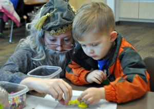 Kim McMilin, a clerk at the Joyce K. Carver Memorial Library in Soldotna, is barely recognizable in her Dumbledore costume as she helps Carter Wertanen, of Soldotna, during the second annual A Night of Spells — Harry Potter Book Night, which took place at libraries, bookstores and schools around the world Thursday. The Kenai Community Library held a similar event.