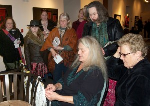 "Photos by Jenny Neyman, Redoubt Reporter. Kay Field Parker demonstrates Ravenstail techniques at the opening reception for her art show, ""Traditional and Contemporary Ravenstail Weavings,"" at the Kenai Visitors and Cultural Center last month."